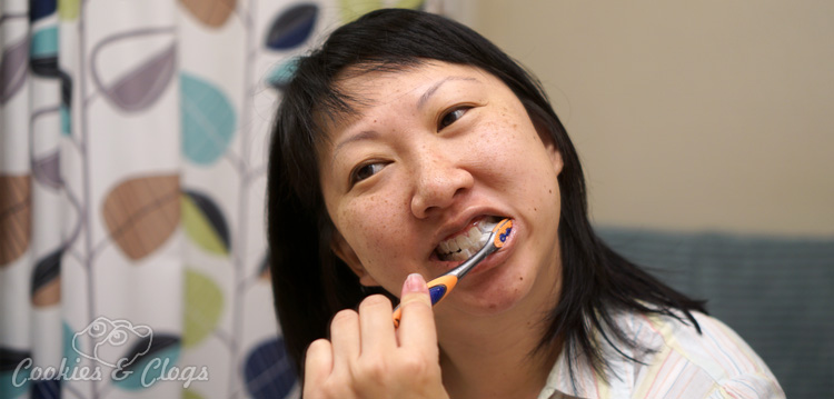 With National Women's Health Week coming up, come take the pledge from Colgate with me to put our health first and post a #MyColgateSelfie photo! See how the Colgate Total Daily Repair toothpaste and mouthwash can help too! Asian woman brushing her teeth.