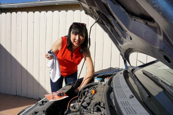 Cars | Road Safety | These five basic car maintenance guidelines are important for every woman / female driver. See how these will make your car last longer, run smoother, you'll save money, and it will help keep you and your family safer. Asian woman with open hood of car changing headlight bulbs.