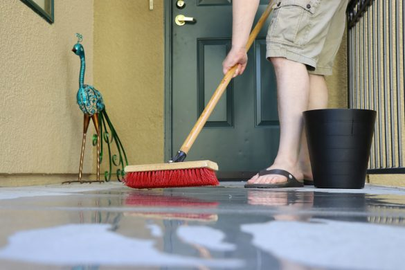 See how to use Clorox bleach for back to school cleaning - scrubbing outside patio with broom.