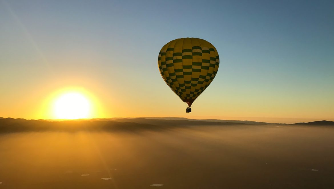 Hot air balloon ride over Napa Valley California at sunrise with clouds