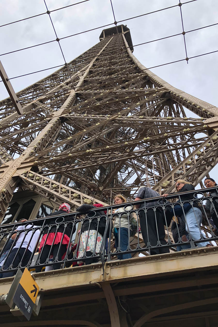 Paris Travel Guide: Top tips for how to visit the top of the Eiffel Tower in Paris France looking up from 2nd second floor